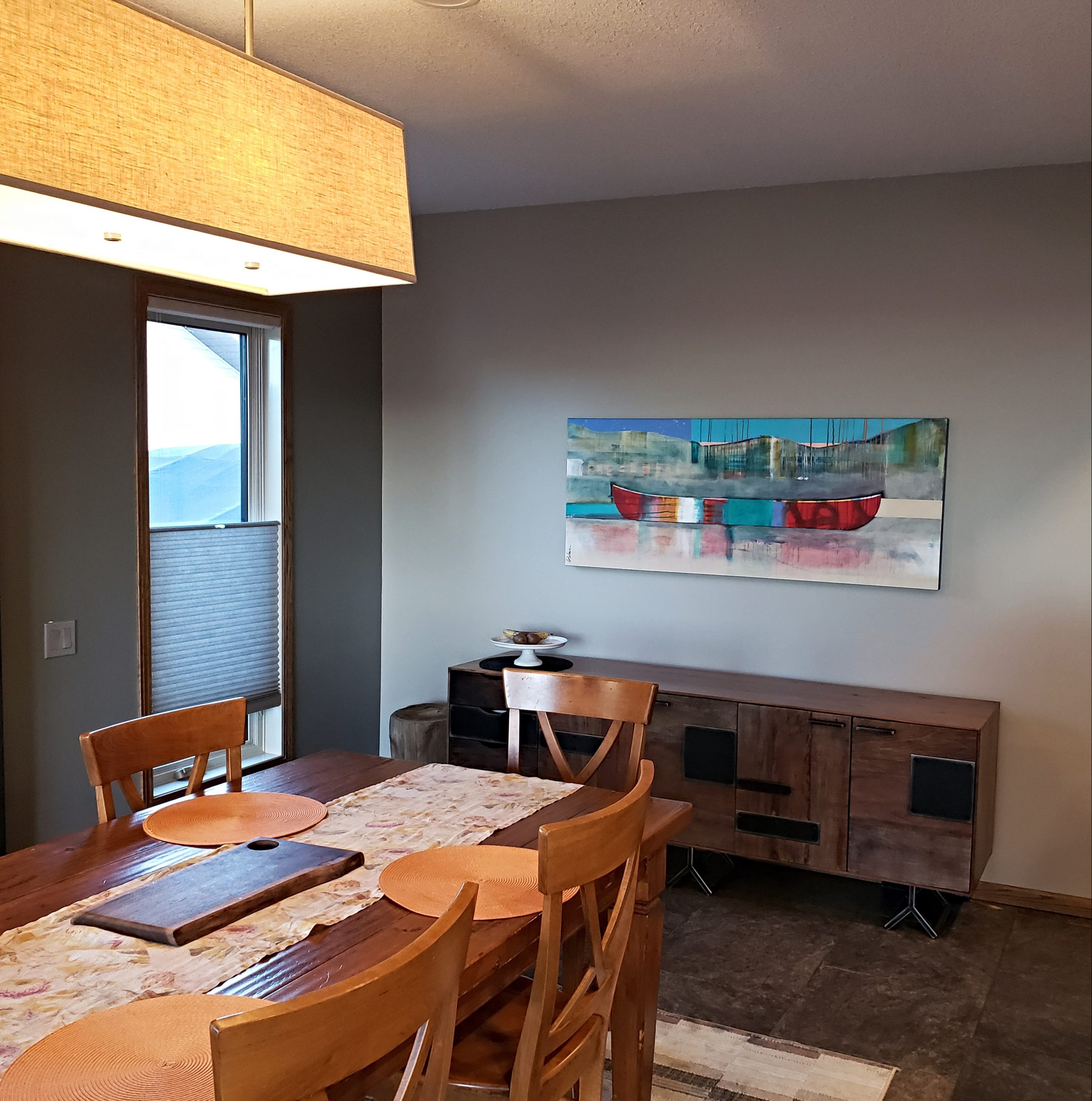 Tu m'amènes vers d'autres rives, mixed media canoe painting by Sylvain Leblanc, installed in its beautiful new prairie home | Effusion Art Gallery + Cast Glass Studio, Invermere BC
