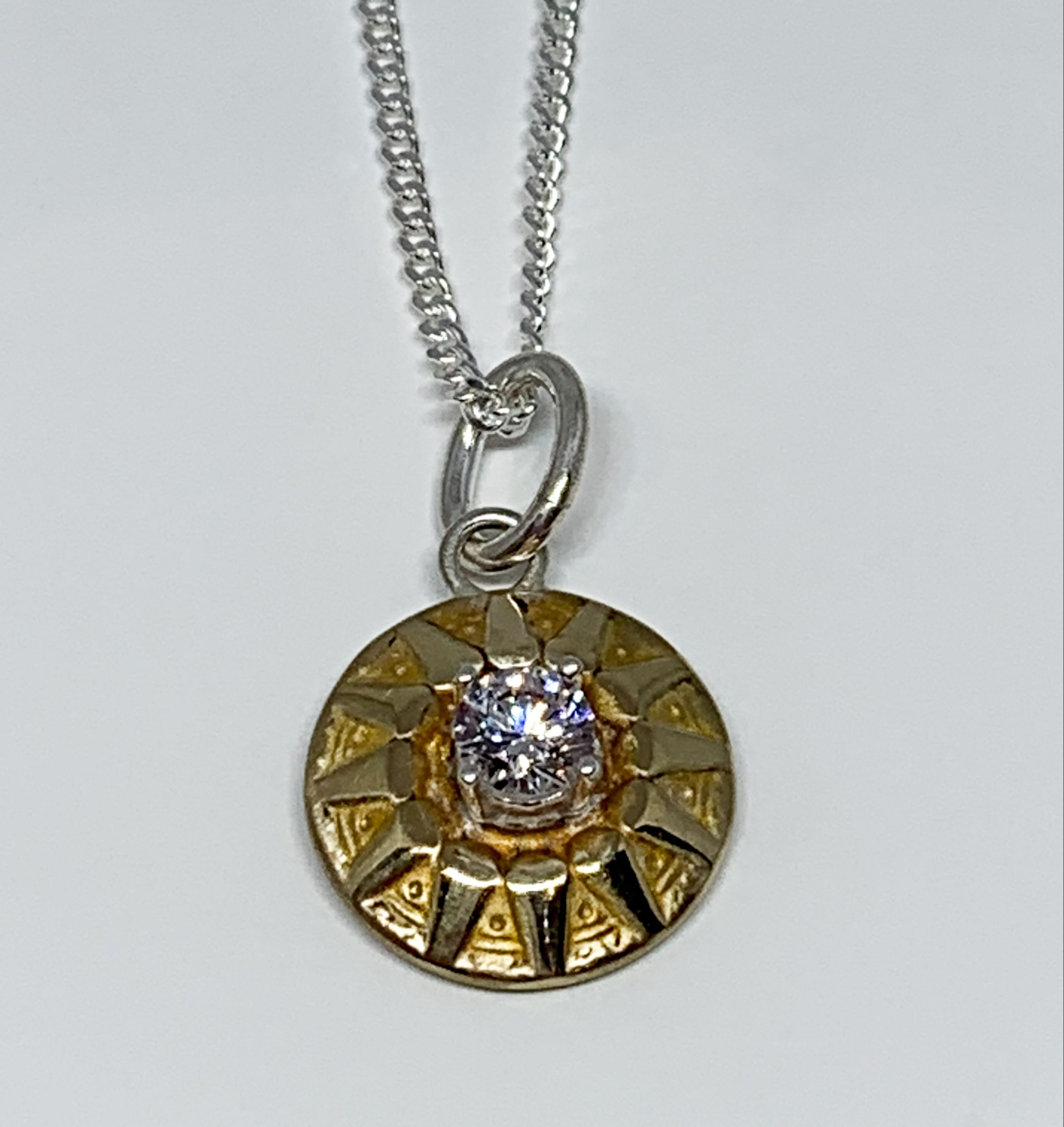 Bronze, sterling silver, and CZ sunburst necklace by Karyn Chopik | Effusion Art Gallery + Cast Glass Studio, Invermere BC